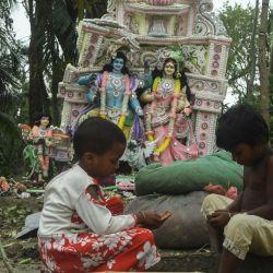 Los niños juegan cerca de un ídolo hindú dañado después de la llegada del ciclón Amphan en el área de Khejuri en East Midnapore, Bengala Occidental, el 21 de mayo de 2020. - Al menos 84 personas murieron cuando el ciclón más feroz que golpeó partes de Bangladesh y el este de India este siglo envió árboles volando y casas aplastadas, con millones apiñados en refugios a pesar del riesgo de coronavirus. (Foto por Dibyangshu SARKAR / AFP)   Foto:AFP