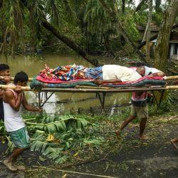 Los residentes llevan Tapas Pramanik (C), de 41 años, después de que una pierna se rompió por la caída de un árbol la noche anterior, en busca de una ambulancia o vehículo para llevarlo al hospital, después del aterrizaje del ciclón Amphan en el área de Khejuri en Midnapore, West Bengala, el 21 de mayo de 2020. - Al menos 22 personas murieron cuando el ciclón más feroz que golpeó partes de Bangladesh y el este de la India este siglo envió árboles volando y aplastó casas, con millones apiñados en refugios a pesar del riesgo de coronavirus. (Foto por Dibyangshu SARKAR / AFP)   Foto:AFP