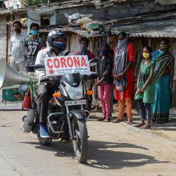 El agricultor Bamandla Ravinder, que recorre su bicicleta en las aldeas del estado de Telangana para dar a conocer el coronavirus COVID-19, viaja mientras la gente lo observa en los barrios bajos de Hyderabad el 21 de mayo de 2020. (Foto de NOAH SEELAM / AFP)   Foto:AFP