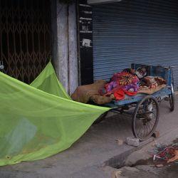 Hombres sin hogar duermen frente a una tienda cerrada en Siliguri el 21 de mayo de 2020. (Foto de DIPTENDU DUTTA / AFP)   Foto:AFP