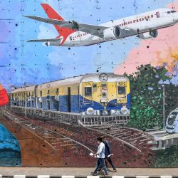 Los peatones pasan junto a un mural que representa varias formas de transporte después de que el gobierno alivió un bloqueo nacional impuesto como medida preventiva contra el coronavirus COVID-19, en Mumbai el 21 de mayo de 2020. - Los viajes aéreos nacionales se reanudarán en India el 25 de mayo después de un El cierre de dos meses impuesto para detener la propagación del coronavirus, dijo el ministro de aviación el 20 de mayo, en una mayor relajación de las restricciones de bloqueo nacional. (Foto por INDRANIL MUKHERJEE / AFP)   Foto:AFP