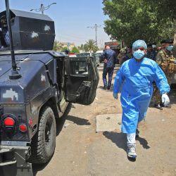 Un médico pasa junto a vehículos del ejército iraquí que bloquea la entrada al suburbio de Sadr City, capital de Bagdad, el 21 de mayo de 2020, durante una campaña de pruebas de COVID-19 como parte de las medidas tomadas por las autoridades destinadas a contener la propagación del nuevo coronavirus. . - Ciertos vecindarios en la capital iraquí, Bagdad, comenzaron un cierre total durante dos semanas a partir de ayer, en reacción a un aumento en las infecciones por coronavirus debido a que las restricciones se relajaron. (Foto por AHMAD AL-RUBAYE / AFP)   Foto:AFP