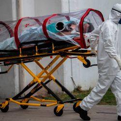 Los paramédicos de la Cruz Roja llevan a un paciente sospechoso de estar infectado con el nuevo coronavirus al Hospital de Traumatología del Instituto Mexicano del Seguro Social (IMSS), en la Ciudad de México, el 20 de mayo de 2020. (Foto de PEDRO PARDO / AFP)   Foto:AFP