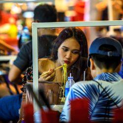 La gente come en un restaurante callejero que implementa el distanciamiento social con divisores de plástico después de que el gobierno tailandés relajó las medidas para combatir la propagación del nuevo coronavirus COVID-19, en el barrio chino de Bangkok el 21 de mayo de 2020. - Tailandia continuó flexibilizando las restricciones relacionadas con el COVID-19 nuevo coronavirus el 17 de mayo al permitir la reapertura de varios negocios, pero advirtió que las medidas más estrictas se volverían a imponer si los casos aumentaran nuevamente. (Foto por Mladen ANTONOV / AFP)   Foto:AFP