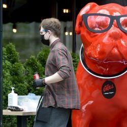 Un camarero con una máscara protectora lleva bebidas a los clientes mientras pasa junto a una escultura de perro, en un café callejero reabierto en el centro de Kiev el 21 de mayo de 2020, mientras Ucrania levanta parcialmente algunas restricciones impuestas para frenar la propagación del COVID. 19 brote, causado por el nuevo coronavirus. (Foto por Sergei SUPINSKY / AFP)   Foto:AFP