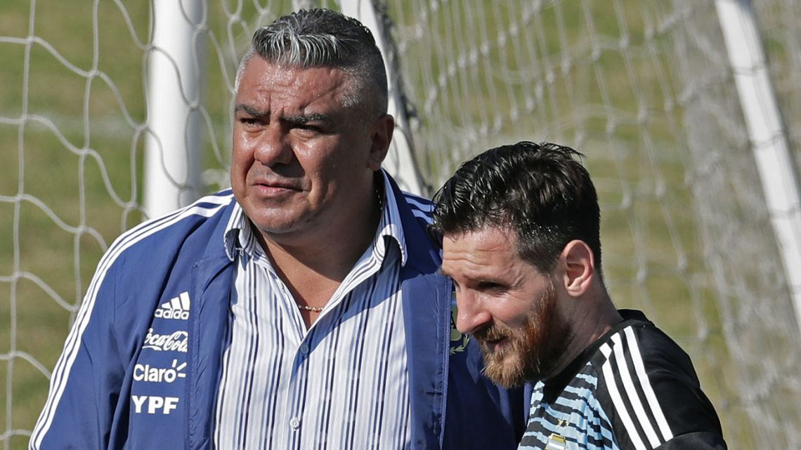 In this file photo taken on May 27, 2018, Lionel Messi stands with AFA President Claudio Tapia, during a training session at the Tomas Duco stadium in Buenos Aires, ahead of the FIFA World Cup. Tapia was re-elected on May 19, 2020, for a five-year-term in a virtual assembly, that had him as the only candidate.