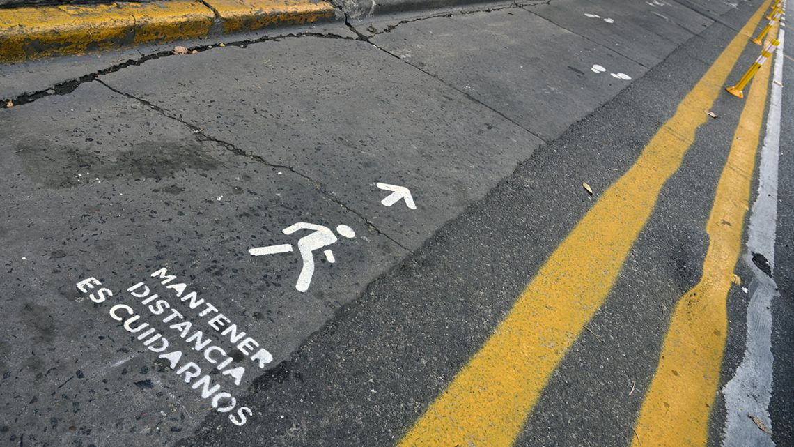 A sign on a pedestrian lane reminds people to keep prudential distance between each other due to the Covid-19 coronavirus pandemic, on Corrientes Avenue in Buenos Aires, on May 18, 2020. Latin American cities are beginning to implement their 'new normal' with the introduction of bicycle lanes, widened sidewalks and distance signs, to overcome the COVID-19 emergency in urban spaces already affected by overcrowding, crowded transport and pollution.