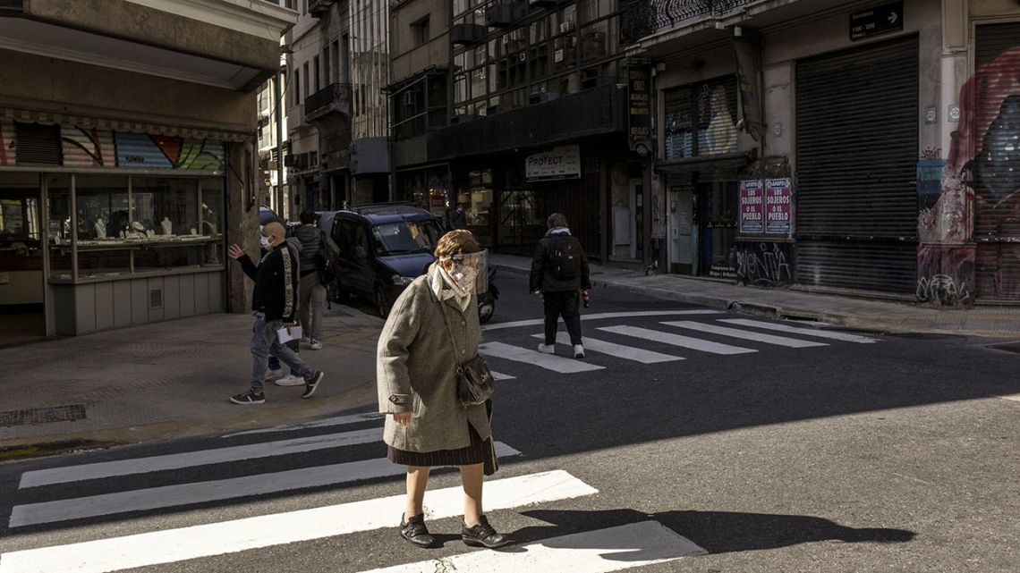 A woman wearing a face mask crosses the street in Buenos Aires.