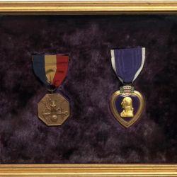 Esta insignia fue realizada en forma de corazón de color purpura con el borde en bronce.