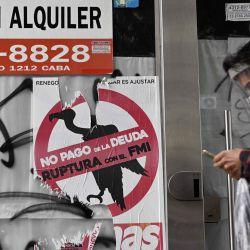 Un hombre pasa junto a una señal contra el pago de la deuda con el FMI pegado en una tienda en alquiler durante el cierre impuesto por el gobierno contra la propagación del nuevo coronavirus, en Buenos Aires, el 22 de mayo de 2020. - Argentina se tambaleaba en el al borde de un segundo incumplimiento en este siglo el viernes, cuando se acerca la fecha límite para un reembolso de intereses de $ 500 millones. El jueves, el Ministerio de Economía anunció que había pospuesto las conversaciones por segunda vez con los acreedores internacionales sobre la reestructuración de la deuda de $ 66 mil millones, esta vez hasta el 2 de junio. Se suponía que las negociaciones se completarían antes del 8 de mayo, pero ya se habían extendido hasta Viernes. (Foto por JUAN MABROMATA / AFP)   Foto:AFP