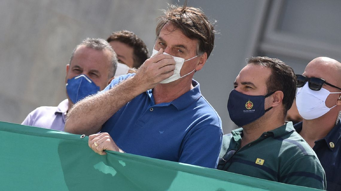 Brazil's President Jair Bolsonaro, wearing a protective face mask as a precaution against the spread of the new coronavirus, joins in a protest against the Supreme Court and Brazil's National Congress, in Brasilia, Brazil.