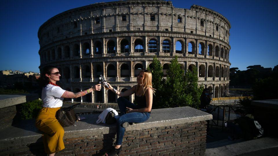 Roma, Italia: Dos mujeres brindan con cerveza junto al monumento del Coliseo