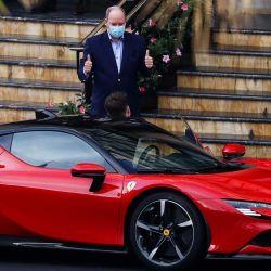 El Príncipe Alberto II de Mónaco (C), usa una máscara protectora mientras reacciona antes de subirse a un automóvil Ferrari durante el rodaje del cortometraje de Claude Lelouch  | Foto:AFP