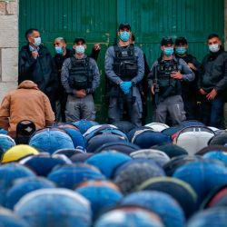 Las fuerzas de seguridad israelíes, vestidas con máscaras debido a la pandemia del coronavirus COVID-19, observan cómo los fieles palestinos se reúnen para asistir a las oraciones de Eid al-Fitr, la fiesta musulmana que comienza en la conclusión del mes de ayuno sagrado del Ramadán, fuera del cerró el complejo de la mezquita de Aqsa en la ciudad vieja de Jerusalén el 24 de mayo de 2020. - Los musulmanes de todo el mundo comenzaron a marcar un sombrío Eid al-Fitr, muchos bajo el bloqueo del coronavirus, pero las restricciones laxas ofrecen un respiro a los fieles en algunos países a pesar del temor a las infecciones por las nubes. La mezquita Al-Aqsa de Jerusalén, el tercer sitio más sagrado del Islam, reabrirá a los fieles solo después de Eid, dijo su órgano rector. (Foto por AHMAD GHARABLI / AFP) | Foto:AFP