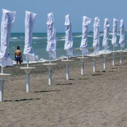 Una mujer camina a lo largo de la costa en una playa en Ostia, al oeste de Roma, el 24 de mayo de 2020 mientras el país alivia las medidas de bloqueo tomadas para frenar la propagación de la pandemia COVID-19, causada por el nuevo coronavirus. - Los restaurantes y las iglesias reabrieron sus puertas en Italia a partir del 18 de mayo de 2020 como parte de una nueva ola de encierro en Europa y un regreso gradual a la normalidad después de dos meses de encierro. (Foto de Andreas SOLARO / AFP) | Foto:AFP