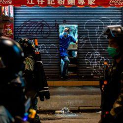 Un hombre se asoma de una tienda mientras la policía realiza una operación de despacho en el distrito de Causeway Bay de Hong Kong el 24 de mayo de 2020, durante las protestas contra una propuesta para promulgar una nueva legislación de seguridad en Hong Kong. - Se espera que la legislación propuesta prohíba la traición, la subversión y la sedición, y sigue a las reiteradas advertencias de Beijing de que ya no tolerará la disidencia en Hong Kong, que fue sacudida por meses de protestas antigubernamentales masivas, a veces violentas, el año pasado. (Foto por ISAAC LAWRENCE / AFP) | Foto:AFP