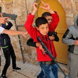 Los niños palestinos juegan con pistolas de juguete de plástico mientras celebran el primer día de Eid al-Fitr, la fiesta musulmana que comienza al concluir el mes del ayuno sagrado del Ramadán, en la ciudad vieja de la ciudad de Hebrón en el oeste ocupado. Banco el 24 de mayo de 2020. (Foto de HAZEM BADER / AFP) | Foto:AFP