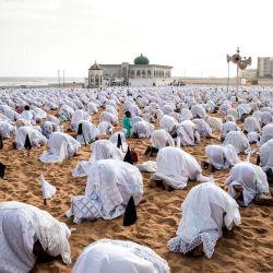 Los seguidores de la comunidad Layene con máscaras protectoras rezan en la playa frente a la Mezquita Yoff Layene, durante la festividad islámica de Korite en Dakar, Senegal, el 24 de mayo de 2020, Korite marca el fin del mes sagrado musulmán del Ramadán. (Foto por JOHN WESSELS / AFP) | Foto:AFP