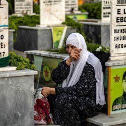 Una mujer llora en la tumba de un luchador kurdo asesinado con las Fuerzas Democráticas Sirias (SDF), en la víspera de Eid el-Fitr, la fiesta musulmana que marca el final del mes de ayuno del Ramadán, en un cementerio en el kurdo -mayoría de la ciudad de Qamishli, en la provincia de Hasakeh, en el noreste de Siria, el 23 de mayo de 2020. (Foto de Delil SOULEIMAN / AFP) | Foto:AFP
