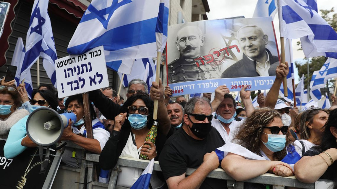 Israeli supporters hold flags and a poster depicting Prime Minister Benjamin Netanyahu alongside French officer Alfred Dreyfus, who had been unjustly convicted of treason in 1895, during a rally outside Netanyahu's residence in Jerusalem on May 24, 2020.