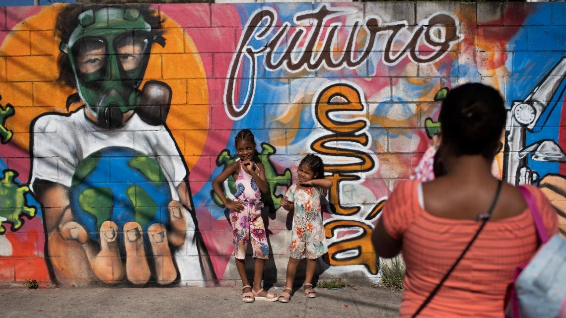 A woman takes photos of her daughters by a mural referencing the Covid-19 pandemic, painted in honour of health workers in Rio de Janeiro, Brazil, Thursday, May 21, 2020. The mural is by graffiti artist Angelo Campos, 39, who has lost two relatives to the new coronavirus.