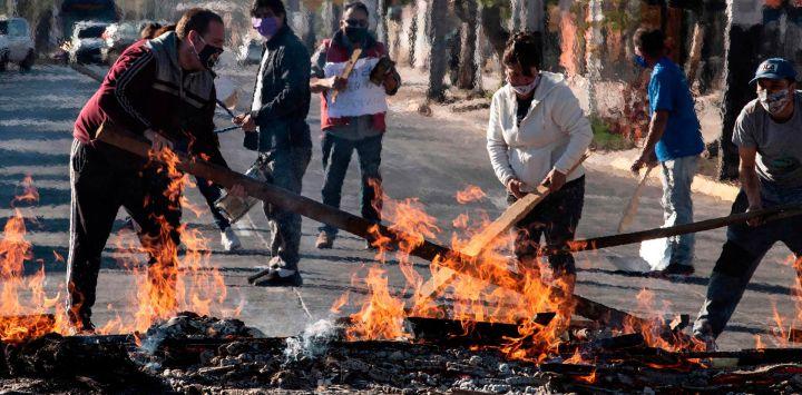 Los manifestantes establecieron una barricada contra incendios durante una protesta contra el gobierno del presidente chileno, Sebastián Pinera, en medio de la pandemia COVID-19, en Santiago, el 25 de mayo de 2020. - Los aldeanos en la populosa comuna en el sur de Santiago, se enfrentaron con la policía después de protestar por la falta de alimentos y trabajo como resultado de la crisis causada por el coronavirus, que mantiene a la capital chilena en cuarentena total. (Foto por MARTIN BERNETTI / AFP)