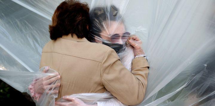 WANTAGH, NUEVA YORK - 24 DE MAYO: Olivia Grant (R) abraza a su abuela, Mary Grace Sileo a través de una tela plástica colgada en una línea de ropa casera durante el fin de semana del Memorial Day el 24 de mayo de 2020 en Wantagh, Nueva York. Es la primera vez que han tenido contacto de cualquier tipo desde que el bloqueo de la pandemia del coronavirus COVID-19 comenzó a fines de febrero. Al Bello / Getty Images / AFP