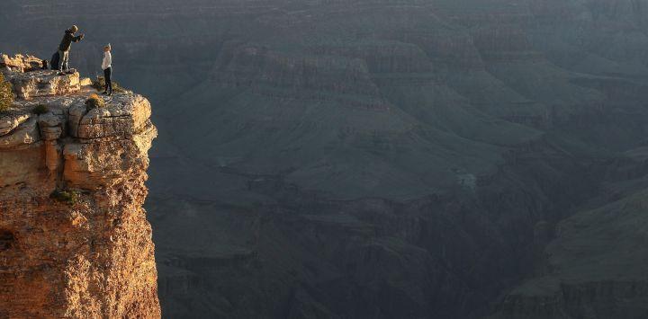 Los visitantes toman fotos después del amanecer en el Día de los Caídos desde el borde sur del Parque Nacional del Gran Cañón, que ha reabierto parcialmente los fines de semana en medio de la pandemia de coronavirus (COVID-19), el 25 de mayo de 2020 en el Parque Nacional del Gran Cañón, Arizona. El parque ha abierto durante horas limitadas y tiene acceso los últimos dos fines de semana a pesar de las preocupaciones de que la mezcla de visitantes podría contribuir a la propagación del virus COVID-19. Los críticos señalan que la vecina Nación Navajo actualmente sufre la tasa más alta de infección por COVID-19 en la nación per cápita y algunos viajeros tendrían que pasar por la nación para llegar al parque. Mario Tama / Getty Images / AFP