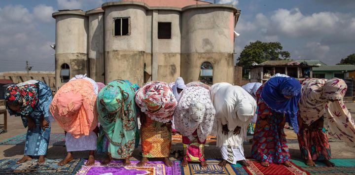 Un grupo de mujeres musulmanas rezan en una azotea en Nima, Accra, el 24 de mayo de 2020 durante las celebraciones de Eid al-Fitr. (Foto por Nipah Dennis / AFP)