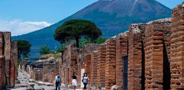 Los visitantes caminan por el sitio arqueológico de Pompeya en la parte inferior del volcán Monte Vesubio (parte posterior) el 26 de mayo de 2020, mientras el país alivia su bloqueo para frenar la propagación de la infección por COVID-19, causada por el nuevo coronavirus. - El sitio arqueológico de fama mundial de Italia, Pompeya, reabrió al público el 26 de mayo, pero con turistas extranjeros que aún tienen prohibido viajar a Italia hasta junio, el sitio que atrajo a menos de 4 millones de visitantes en 2019 espera que, por ahora, los turistas italianos puedan hasta al menos una fracción de la diferencia. (Foto por Tiziana FABI / AFP)