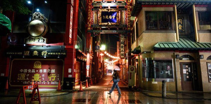 Una mujer camina con un paraguas en el área de Chinatown de Yokohama el 26 de mayo de 2020, un día después de que el gobierno japonés levantó un estado de emergencia a nivel nacional. - Japón levantó un estado de emergencia a nivel nacional sobre el coronavirus el 25 de mayo, reabriendo gradualmente la tercera economía más grande del mundo a medida que los funcionarios del gobierno advirtieron que aún era necesaria la precaución para evitar otra ola. (Foto por Philip FONG / AFP)