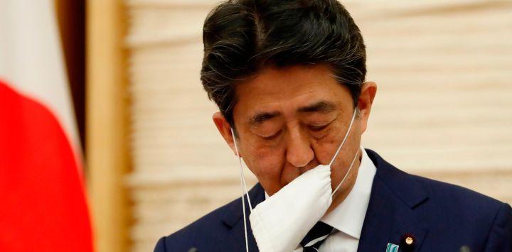 El primer ministro de Japón, Shinzo Abe, se quita la máscara facial cuando comienza una conferencia de prensa en Tokio el 25 de mayo de 2020. - Japón levantó un estado de emergencia a nivel nacional sobre el coronavirus el 25 de mayo, reabriendo gradualmente la tercera economía más grande del mundo como advirtieron los funcionarios del gobierno todavía era necesario tener precaución para evitar otra ola. (Foto por KIM KYUNG-HOON / PISCINA / AFP)