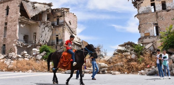 Un niño monta un caballo cerca de la Ciudadela de Alepo en el tercer día de vacaciones de Eid al-Fitr, ya que las restricciones de coronavirus se alivian en medio de la pandemia de COVID-19, en el norte de Siria, el 26 de mayo de 2020. (Foto de - / AFP)