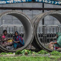 Las mujeres se refugian dentro de una red de alcantarillado durante una llovizna en Dhaka el 27 de mayo de 2020. (Foto de MUNIR UZ ZAMAN / AFP) | Foto:AFP