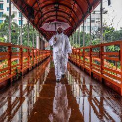 n hombre que usa equipo de protección como medida preventiva contra el coronavirus COVID-19 camina sobre una pasarela en Dhaka el 27 de mayo de 2020. (Foto por MUNIR UZ ZAMAN / AFP) | Foto:AFP