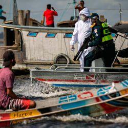 Un trabajador médico del gobierno, en una operación conjunta con la policía militar, se prepara para registrar a un pasajero en un bote en la bahía Melgaco, al suroeste de la isla de Marajo, estado de Pará, Brasil, el 27 de mayo de 2020. - Personas a bordo de pequeñas embarcaciones, A los ferries y barcos en el río se les revisó la temperatura corporal mientras las autoridades intentaban combatir el nuevo coronavirus. (Foto por TARSO SARRAF / AFP) | Foto:AFP