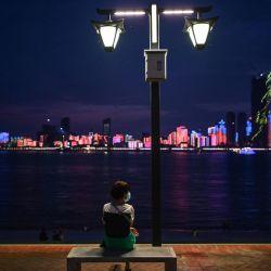 Una mujer con una máscara facial mira a su alrededor mientras se sienta en un paseo junto al río Yangtze en Wuhan, la provincia central de Hubei de China el 27 de mayo de 2020. - El ministro de Relaciones Exteriores de China dijo el 24 de mayo que el país estaba  | Foto:AFP