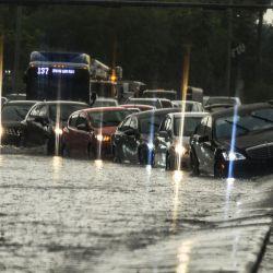 Una persona golpea el automóvil en el divisor de la carretera en el agua inundada mientras llueve intensamente en Miami, el 26 de mayo de 2020. - Los residentes del sur de Florida no pudieron disfrutar de la reciente reapertura de restaurantes, negocios y playas después de casi dos meses de cuarentena debido a la pandemia: tres días seguidos de fuertes lluvias, que alcanzaron 6 pulgadas el 26 de mayo, causaron graves inundaciones en Miami y otras ciudades costeras afectadas por el aumento del nivel del mar. (Foto por CHANDAN KHANNA / AFP) | Foto:AFP