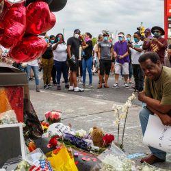Un hombre reza frente a un monumento improvisado en honor a George Floyd, quien murió bajo custodia el 26 de mayo de 2020 en Minneapolis, Minnesota. - Un video de un hombre negro esposado muriendo mientras un oficial de Minneapolis se arrodilló en su cuello por más de cinco minutos provocó un nuevo furor en los Estados Unidos por el tratamiento policial de afroamericanos el martes. El alcalde de Minneapolis, Jacob Frey, despidió a cuatro policías tras la muerte bajo custodia de George Floyd el lunes cuando el sospechoso fue presionado sin camisa en una calle de Minneapolis, con la rodilla de un oficial en el cuello. (Foto por Kerem Yucel / AFP) | Foto:AFP