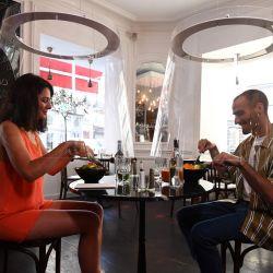 Una pareja almuerza bajo la protección de plexiglás diseñada por Christophe Gernigon en el restaurante H.A.N.D, el 27 de mayo de 2020 en París, mientras Francia alivia las medidas de bloqueo tomadas para frenar la propagación de la pandemia COVID-19, causada por el nuevo coronavirus. (Foto por ALAIN JOCARD / AFP) | Foto:AFP
