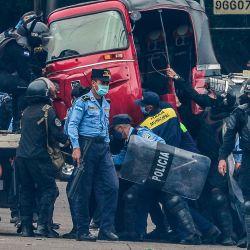 Miembros de la policía antidisturbios hondureña confiscan un mototaxi durante una protesta de taxistas y conductores de mototaxi que demandan alimentos y una ayuda económica del gobierno de Juan Orlando Hernández, en Tegucigalpa, el 27 de mayo de 2020, en medio de la nueva pandemia de coronavirus, COVID-19. - Según informes oficiales, 4401 personas han sido infectadas y 188 han muerto por COVID-19 en Honduras hasta el momento. (Foto por ORLANDO SIERRA / AFP) | Foto:AFP