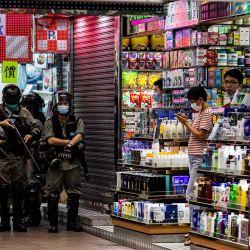 La policía hace guardia en una esquina para disuadir a los manifestantes pro-democracia de bloquear las carreteras en el distrito de Mongkok de Hong Kong el 27 de mayo de 2020, mientras la legislatura de la ciudad debate sobre una ley que prohíbe insultar el himno nacional de China. (Foto por ISAAC LAWRENCE / AFP) | Foto:AFP
