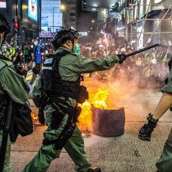 La policía está de guardia en una carretera para disuadir a los manifestantes pro-democracia de bloquear las carreteras en el distrito de Mong Kok de Hong Kong el 27 de mayo de 2020, mientras la legislatura de la ciudad debate sobre una ley que prohíbe insultar el himno nacional de China. - La policía de Hong Kong lanzó una red de arrastre alrededor de la legislatura del centro financiero el 27 de mayo, disparando rondas de bolas de pimienta y arrestando a cientos de personas que protestaron contra un proyecto de ley que prohíbe los insultos al himno nacional de China. (Foto por ISAAC LAWRENCE / AFP) | Foto:AFP