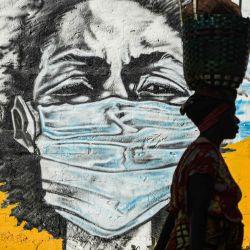 Una mujer tanzana lleva una cesta en la cabeza mientras camina frente a un graffiti pintado por el grupo de artistas Wachata para crear conciencia sobre el uso de máscaras para evitar el riesgo del coronavirus COVID-19 en Dar es Salaam el 26 de mayo de 2020. Foto de Ericky BONIPHACE / AFP | Foto:AFP
