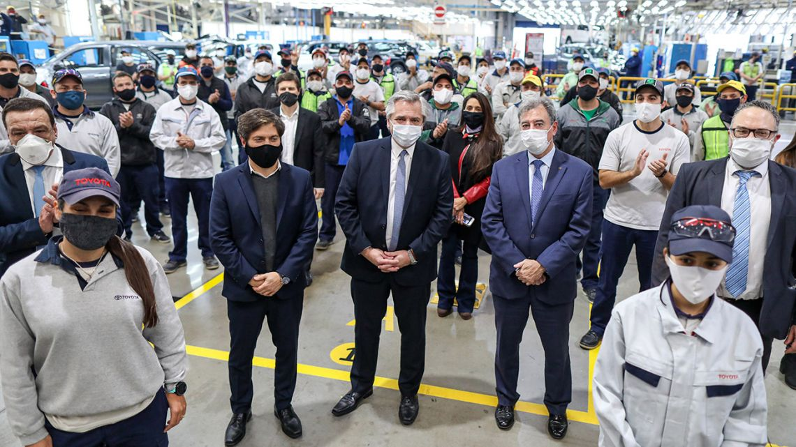Handout photo released by the Presidency shows President Alberto Fernández (centre) and Buenos Aires Province Governor Axel Kicillof (second left) posing with employees from the Toyota production plant in Zárate on May 27, 2020.