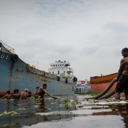 Los trabajadores del astillero tiran de un ferry de carga con una soga antes de realizar trabajos de mantenimiento en Dhaka el 28 de mayo de 2020. (Foto de MUNIR UZ ZAMAN / AFP) | Foto:AFP
