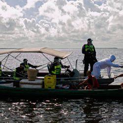 Un trabajador médico del gobierno, en una operación conjunta con la policía militar, revisa a un pasajero en un bote en la bahía de Melgaco, al suroeste de la isla de Marajo, estado de Pará, Brasil, el 27 de mayo de 2020. - Personas a bordo de pequeñas embarcaciones, transbordadores y A los barcos en el río se les revisó la temperatura corporal mientras las autoridades intentaban combatir el nuevo coronavirus. (Foto por TARSO SARRAF / AFP) | Foto:AFP