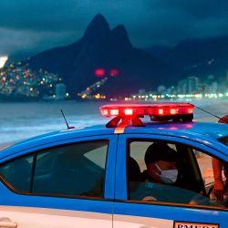 La policía con mascarillas como medida contra la propagación del nuevo coronavirus se ve con su automóvil en la playa de Ipanema en Río de Janeiro, Brasil, el 19 de mayo de 2020. - En medio de la pandemia, continúan las operaciones policiales en la  | Foto:AFP