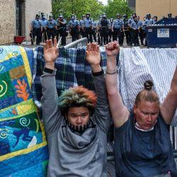 Los manifestantes levantan las manos mientras lloran por los gases lacrimógenos durante una manifestación en un llamado a la justicia para George Floyd después de su muerte, fuera del 3er Recinto Policial el 27 de mayo de 2020 en Minneapolis, Minnesota. - La familia de un hombre afroamericano asesinado por la policía de Minneapolis mientras estaba bajo custodia exigió el miércoles que los oficiales sean acusados de asesinato. Después de una noche de protestas furiosas por la muerte de George Floyd, con la policía disparando gases lacrimógenos y balas de goma en la ciudad del norte de los EE. UU., Su hermana Bridgett Floyd exigió el arresto de los cuatro policías blancos involucrados en su muerte. (Foto por Kerem Yucel / AFP) | Foto:AFP