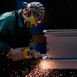 Un empleado trabaja en la fabricación de ataúdes de acero en la Platinum Casket Company en Los Reyes Acaquilpan, México, el 28 de mayo de 2020, en medio de la nueva pandemia de coronavirus. - La compañía diseñó los ataúdes como una alternativa para las familias de las víctimas de COVID-19 que prefieren enterrar a sus fallecidos. El ataúd está hecho de acero, tiene forma de cápsula y todas las paredes están selladas y soldadas para evitar fugas de líquidos. (Foto por CLAUDIO CRUZ / AFP) | Foto:AFP